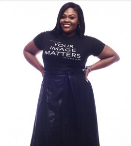 black woman smiling, wearing black t-shirt and black long leather skirt and wearing hair extensions