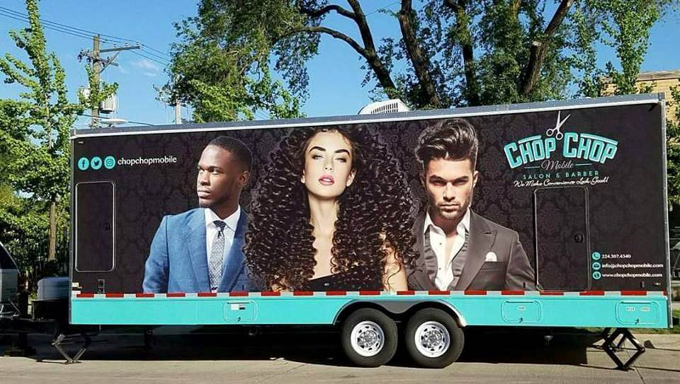 Box trailer outside wrapped with images of two men and one woman