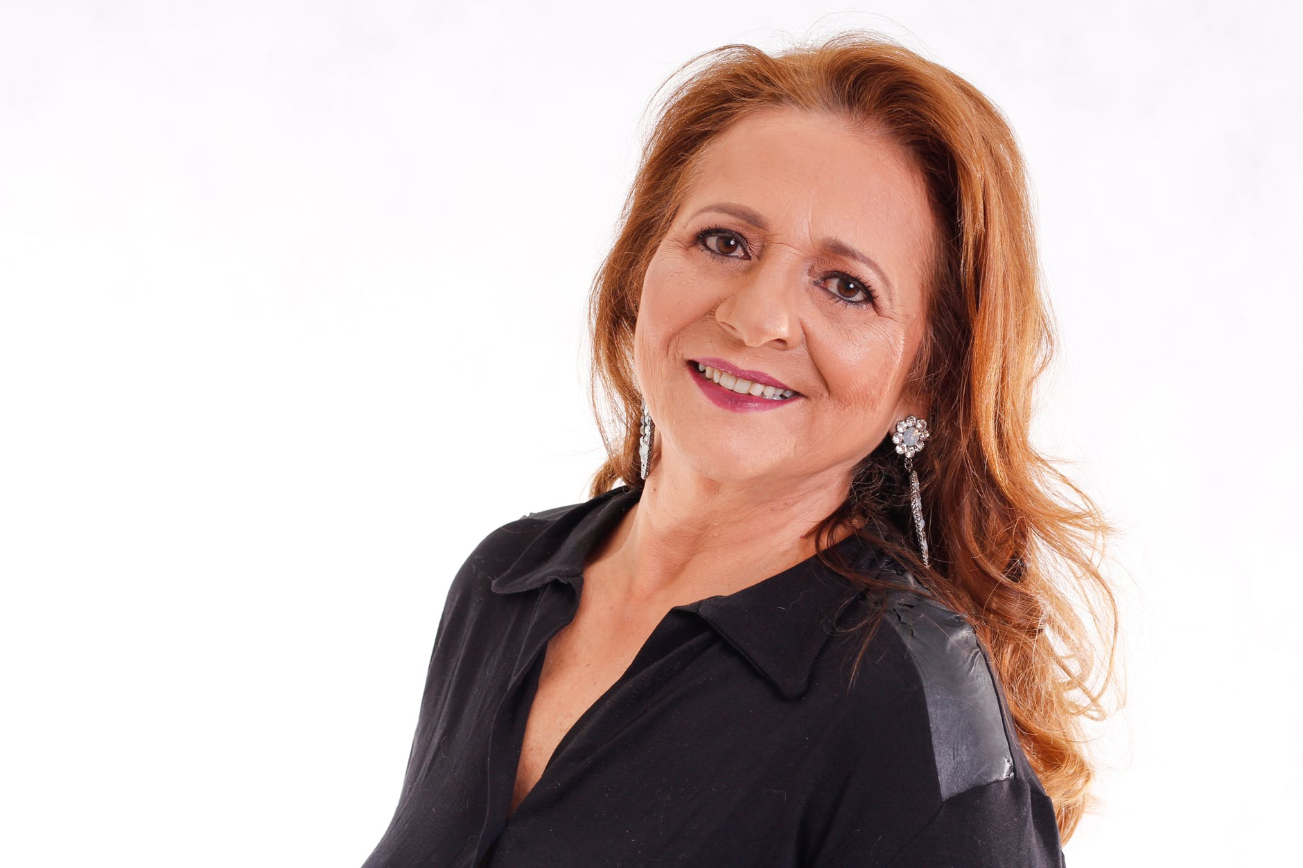 head shot of older woman with long red hair posing in front of white background